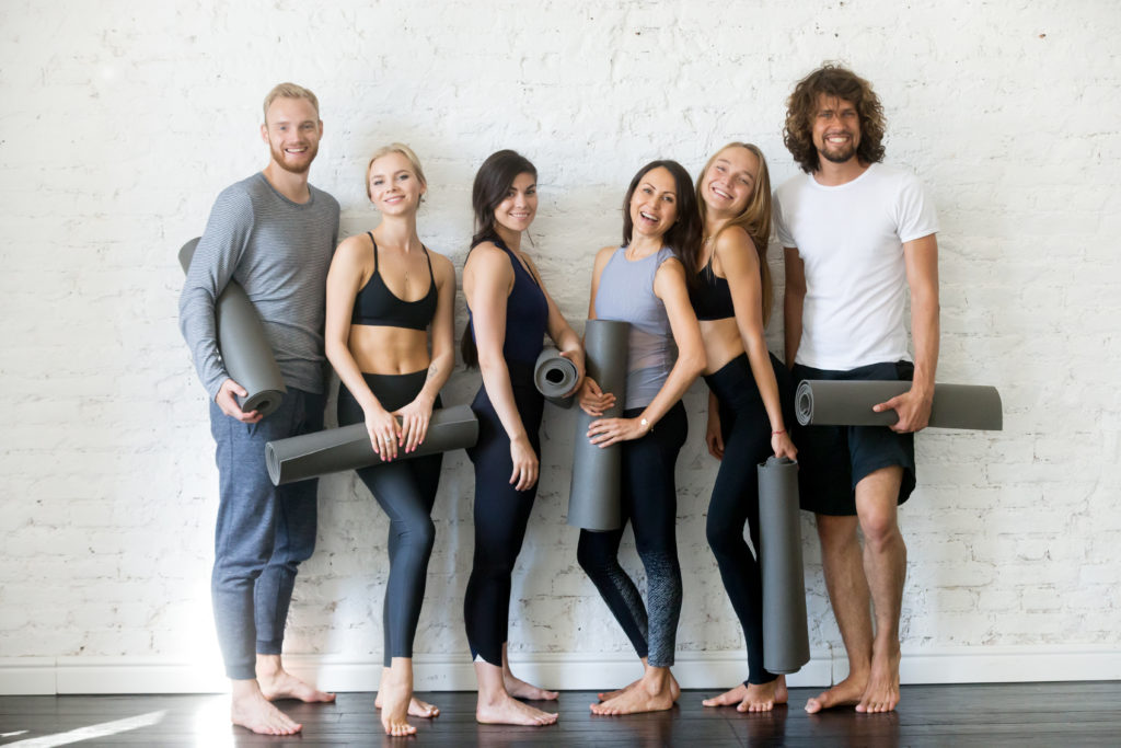 People in leggings holding yoga mats in a yoga shop close to Geneva